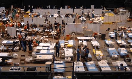 An aerial image of a crowded emergency shelter with many people, beds, and supplies